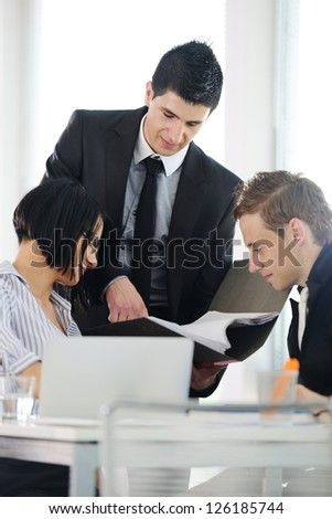 Three business people working at office searching documents and using laptop - stock photo