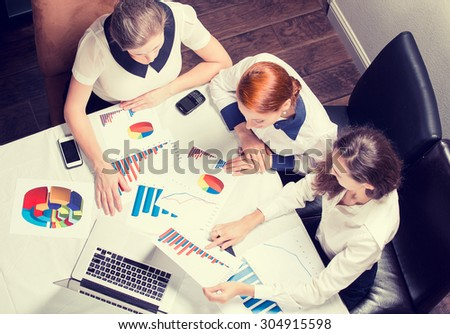 Three business woman investment consultant analyzing company annual financial report balance sheet statement working with documents graphs. Stock market, office, tax, concept. Hands with charts papers