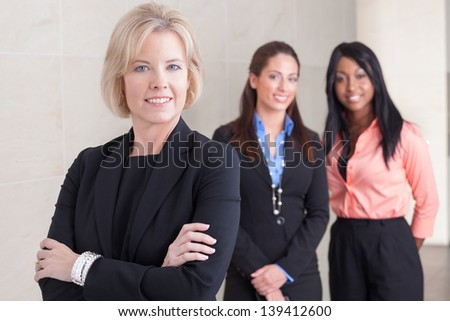 Three business women of varying ethnicities in suits, standing together, smiling and looking at camera, in office - stock photo