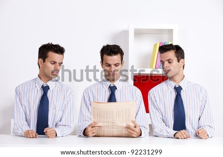 Three businessman at the office peeking and reading a newspaper - stock photo