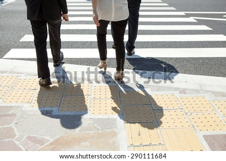 Three Businessman Chatting Whilst Crossing Street