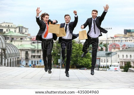 Three businessman jumping with paper bags in her hand on the background of the city - stock photo