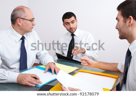 Three businessman, one mature and two young ones sitting at table during meeting