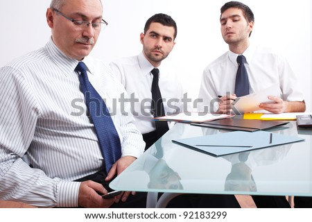 Three businessman, one mature texting using his mobile phone and two young ones sitting at table during meeting - stock photo