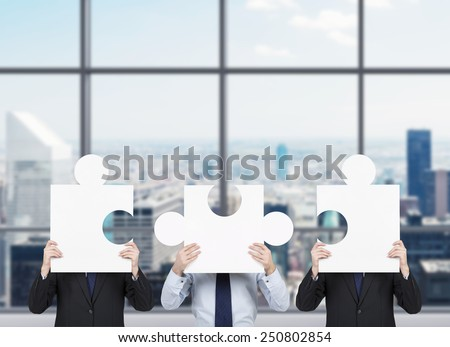 three businessman standing in office holding puzzle - stock photo