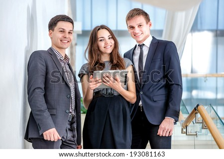 Three businessman standing on the stairs solve business problems. Several young people are at each other and smiling. People hold a tablet in the hands