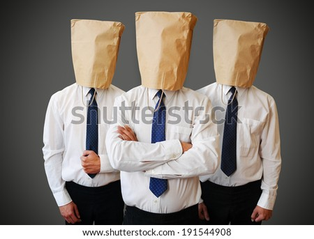 Three businessman with a paper bag on head - stock photo