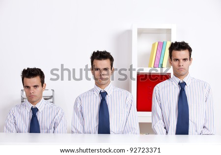 Three businessman with different sizes at the office desk - stock photo