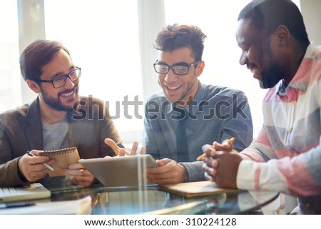 Three businessmen discussing new project at meeting - stock photo