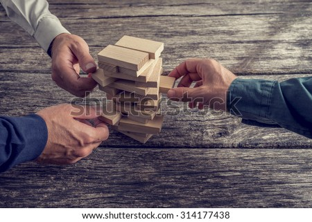 Three Businessmen Hands Playing Wooden Tower Game on Top of a Rustic Wooden Table. Conceptual of Teamwork, Strategy and Vision. - stock photo