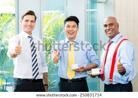 Three businessmen showing the thumbs up celebrating some success - stock photo