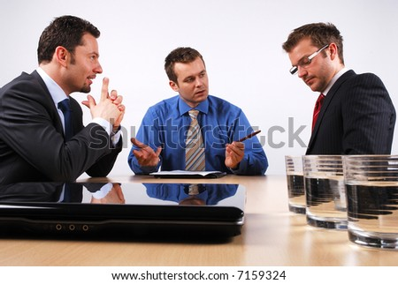 Three businessmen sitting at a table negotiating and signing a contract. - stock photo