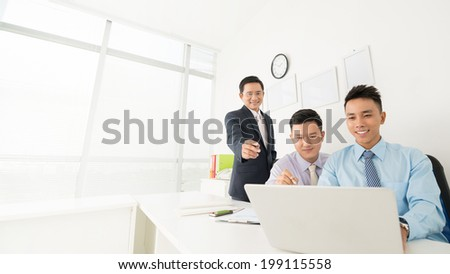 Three businessmen working together in the office - stock photo