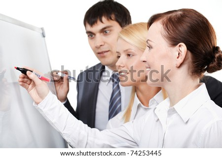 Three businesspeople drawing something on a whiteboard