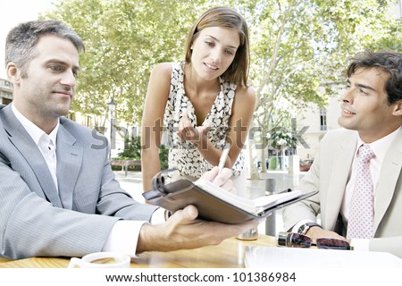 Three businesspeople having a meeting while in a coffee shop'ts terrace in the city. - stock photo