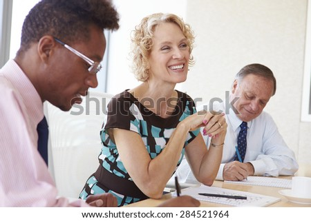 Three Businesspeople Having Meeting In Boardroom