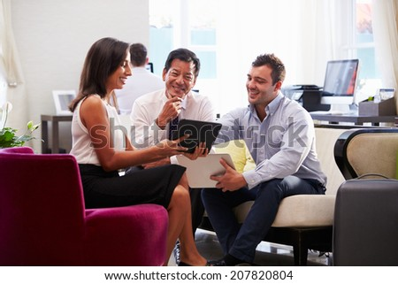 Three Businesspeople Having Meeting In Hotel Lobby - stock photo