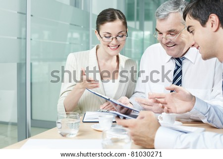 Three businesspeople holding discussion in office