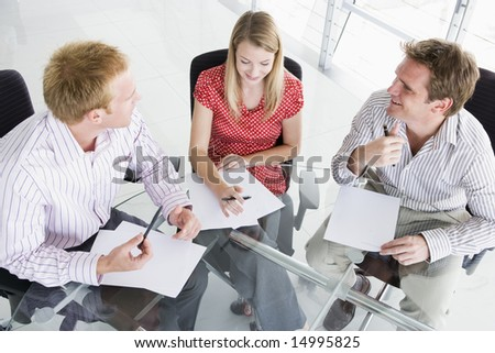Three businesspeople in a boardroom looking at paperwork - stock photo