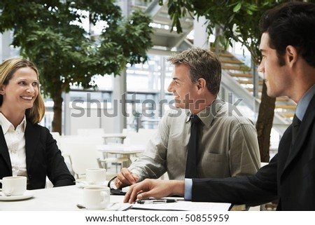 Three businesspeople in meeting, outdoors - stock photo