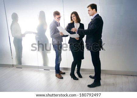 three businesspeople interacting at meeting. beautiful woman with her colleagues