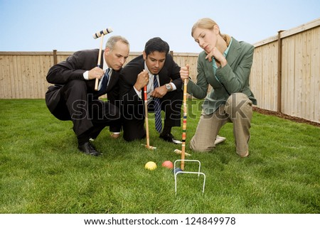 Three businesspeople playing croquet on lawn