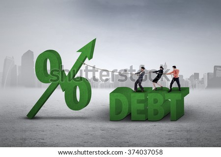 Three businesspeople pulling a percentage symbol with upward arrow and debt word - stock photo