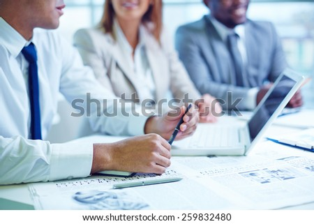 Three businesspeople sitting at table - stock photo