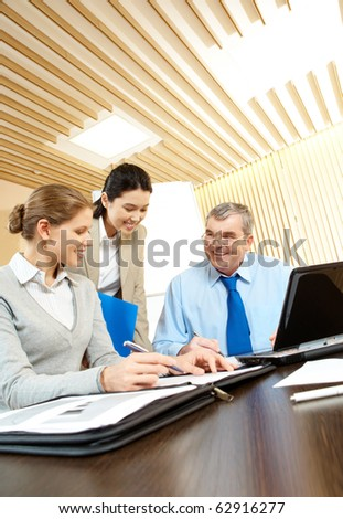 Three businesspeople sitting in the office and smiling - stock photo