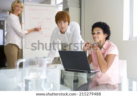 Three businesswomen in meeting room, one at laptop, one by flipchart, smiling, portrait - stock photo