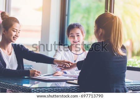 three businesswomen join hand while meeting in office
