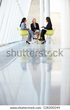 Three Businesswomen Meeting Around Table In Modern Office - stock photo