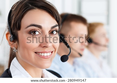 Three call center service operators at work. Portrait of smiling pretty female helpdesk employee with headset at workplace. Effective and efficient business information, help and support concept