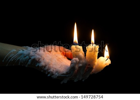 Three candle sticks on fingers burning with wax flow - stock photo