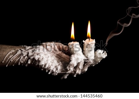 Three candle sticks on fingers burning with wax flow dead artistic conversion - stock photo