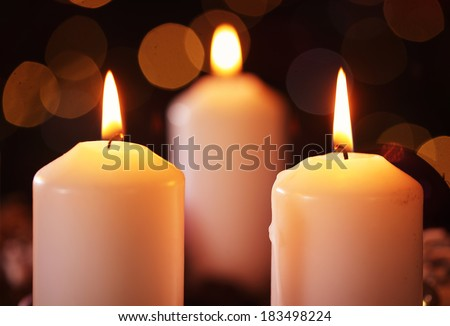 Three candles against abstract bakcground - stock photo