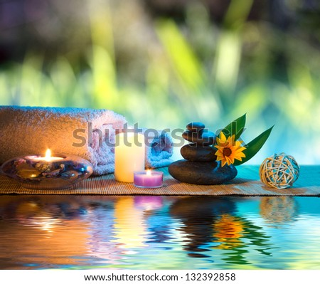 three candles and towels black stones and orange daisy on water - stock photo