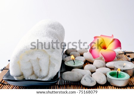 Three candles and white towel on bamboo mat.