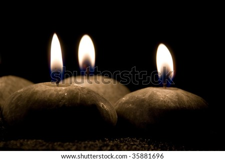 Three candles in the form of stones on a black background - stock photo