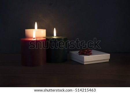 Three candles on a wooden surface with white gift box topped with red ribbon.