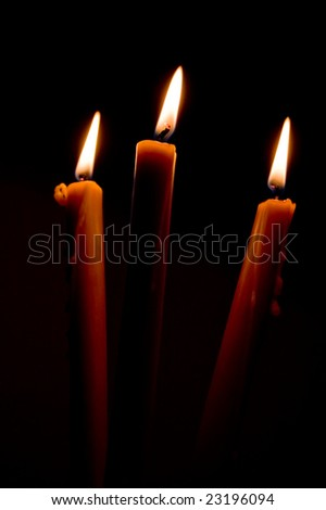 Three candles shining in the dark during Christmas evening. - stock photo