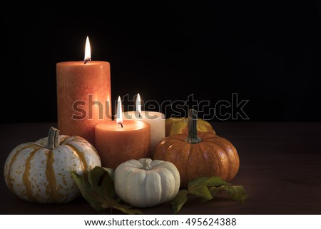Three candles surrounded by gourds with black background and space for copy.