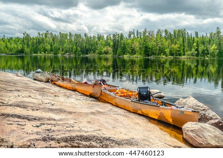 Three canoes line a rocky shore made of igneous rocks in the Boundary Waters Canoe area in the North Woods of Minnesota with beautiful green trees reflecting in the lake behind.