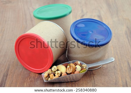 three cans of nuts and spoon on table - stock photo