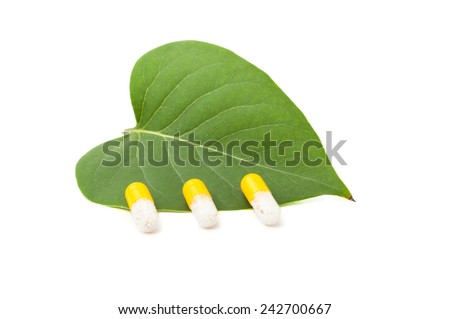Three capsules on green leaf isolated on white background