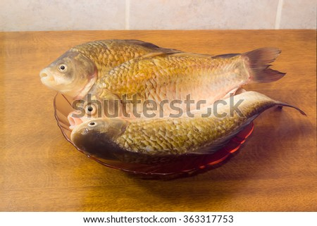 Three carps with peeled scales on red glass dish and prepared for cooking on a light background. Isolation.