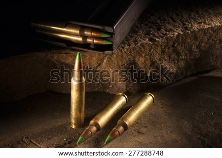 Three cartridges with green tipped bullets and a magazine on rocks - stock photo