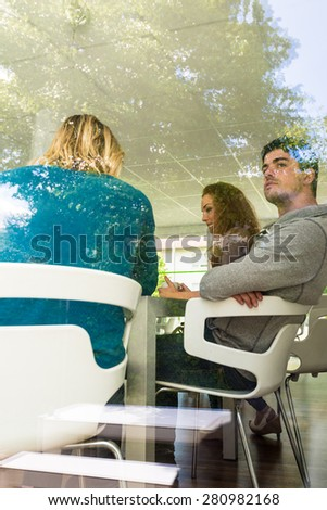 Three casual  business colleagues communicating during coffee break seen through a large window with reflections of the outside - stock photo