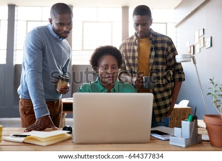Three casually dressed young African business colleagues using a laptop while working together at a table in a modern office