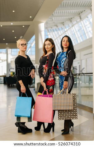 Three charmed women in big mall after shopping. Female wearing dresses with lond sleeves and have many shopping bags in their hands.